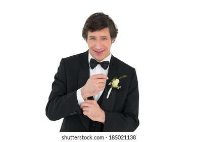 Portrait of smiling groom in tuxedo getting ready over white background