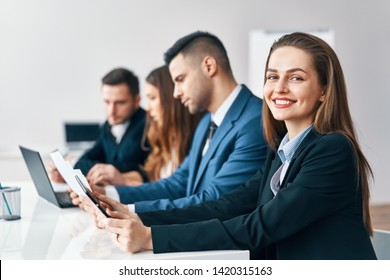 Portrait of smiling group of business people sitting in a row together at table in a modern office. Business team  concept