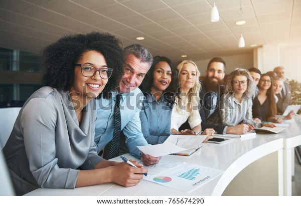 Portrait of a smiling group of diverse corporate colleagues standing in a row together at a table in a bright modern office