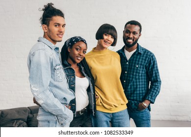portrait of smiling group of multicultural friends standing in room