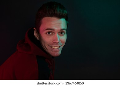 Portrait of a smiling guy in a hoodie, in the studio. Close-up, using green and red back lights.