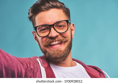 Portrait of smiling Handsome bearded young hipster man with glasses on blue background
