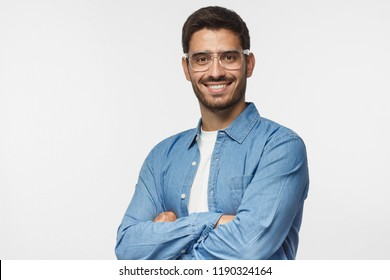 Portrait of smiling handsome business man in casual blue denim shirt standing with crossed arms, isolated on gray background