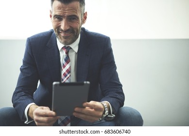 Portrait of smiling handsome executive manager using digital tablet for checking online report sitting in office on promotional background,proud CEO satisfied with occupation and successful project