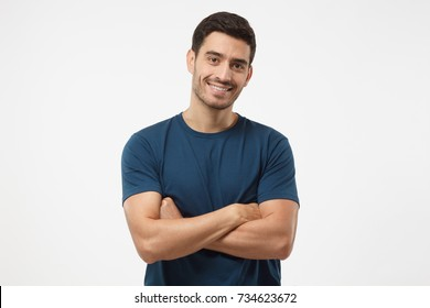 Portrait of smiling handsome guy in blue t-shirt standing with crossed arms isolated on gray background
