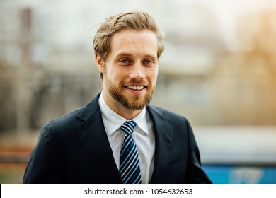 portrait of smiling handsome man, in elegant suit, successful businessman smiling outside, looking to camera