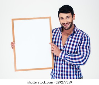 Portrait of a smiling handsome man holding blank board isolated on a white background