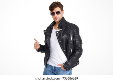 Portrait of a smiling handsome man in a leather jacket and sunglasses showing thumbs up gesture while standing isolated over white background