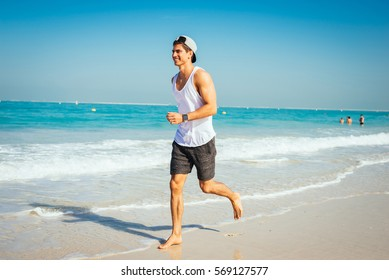 Portrait of a smiling handsome man running on the beach and enjoying the view of the ocean.