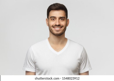 Portrait of smiling handsome young man in white t-shirt, looking at camera, isolated on gray background