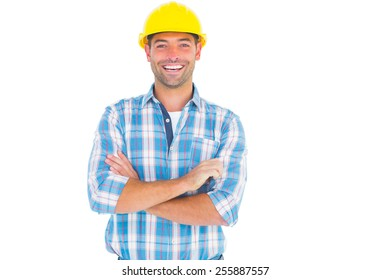Portrait of smiling handyman wearing hardhat while standing arms crossed on white background