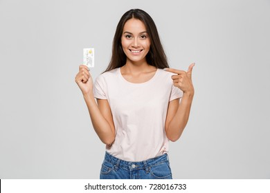 Portrait of a smiling happy asian woman in eyeglasses pointing finger at a pill in plastic cover isolated over white background
