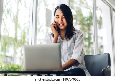 Portrait of smiling happy beautiful asian woman relax using technology of smartphone and looking at laptop sitting on chair.Young hipster asian girl freelancer using laptop computer in cafe