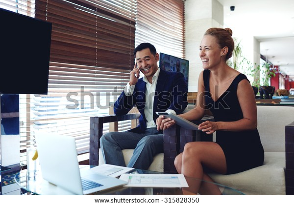 Portrait of a smiling happy businesswoman holding digital tablet while her men colleague calling with smart phone,young successful male and female preparing for the conference using technology gadgets
