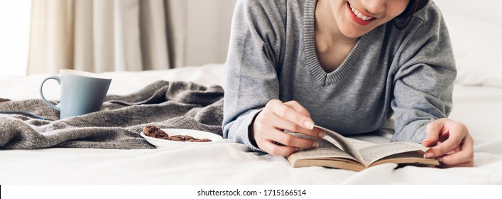 Portrait of smiling happy cheerful beautiful pretty asian woman relaxing reading a book enjoy of rest.Young student girl studying with book in holiday morning vacation on bed at home with copy space