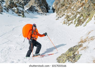 Portrait of a smiling happy freeride backcountry skier with an opened avalanche dowel abs in a backpack.