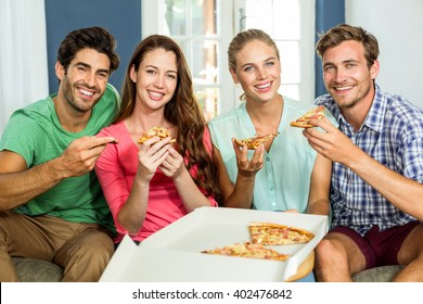 Portrait of smiling happy friends eating pizza at home