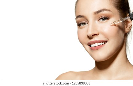 Portrait of smiling happy girl applying face oil and enjoying treatment. Cleansing concept. Copy space in left side. Cute model with attractive appearance on white background