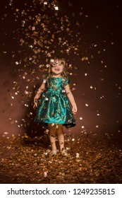 portrait of smiling happy girl in christmas decoration falling golden confetti background