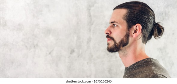 Portrait of smiling happy handsome bearded hipster man model with copy space banner for adding text on white wall background