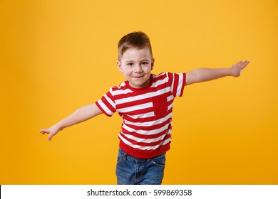 Portrait of a smiling happy kid standing with hands spread wide isolated on the orange background