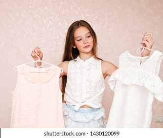Portrait of smiling happy little girl child schoolgirl choosing dresses clothes and having fun