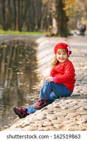 Portrait of a smiling happy little girl sitting on the shore near the river outdoors.