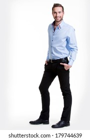 Portrait of smiling happy man in blue shirt and black pants - isolated on white.