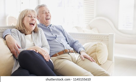 Portrait of smiling happy older couple laughing at something on their couch with space for text