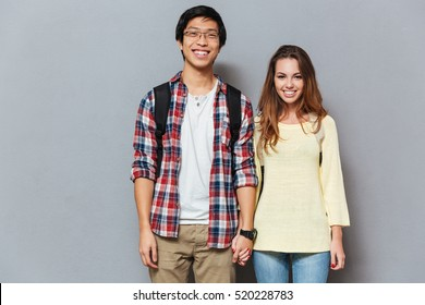 Portrait of a smiling happy student couple with backpacks standing and holding hands isolated on the gray background