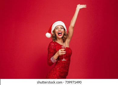 Portrait of a smiling happy woman in christmas hat and dress holding champagne glass while standing with hand outstretched isolated over red background