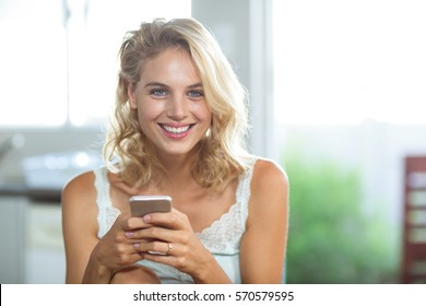 Portrait of smiling happy woman holding mobile phone at home