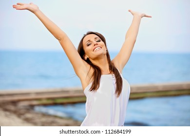 Portrait of a smiling happy woman raising her arms on the beach