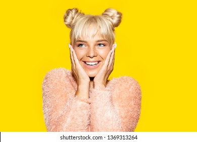 Portrait of smiling happy woman touching face with natural makeup. Female with tied up blonde hair looking away with smirk. Isolated on yellow background