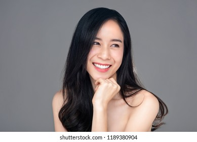 Portrait of smiling happy young beautiful fair skin asian woman in studio gray background for skin care and beauty concepts
