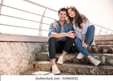 Portrait of a smiling happy young couple looking at camera and sitting at the seaside
