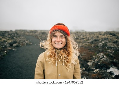 Portrait of smiling happy young woman with blonde hair and cute smile, look into camera on cold windy day during iceland roadtrip adventure. wears raincoat, hair blows in wind. Outdoor vibes lifestyle