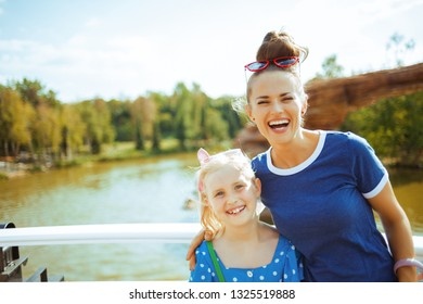 Portrait of smiling healthy mother and daughter travellers on river boat having river voyage.