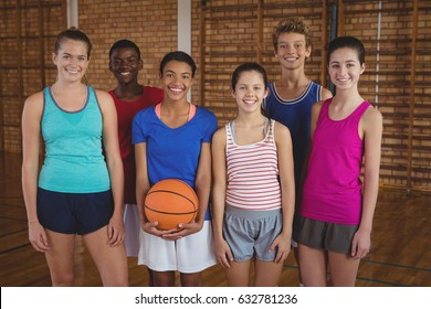Portrait of smiling high school team standing in the basketball court
