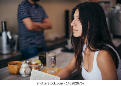 Portrait of a smiling hipster girl is holding book while resting in cafe
