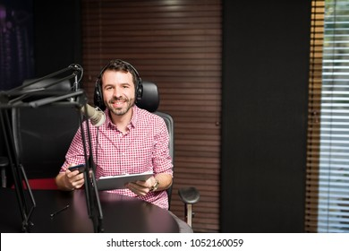 Portrait of smiling hispanic male radio presenter with clipboard hosting a show at radio station