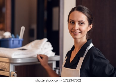 A portrait of a smiling hotel maid with a cleaning cart and clea