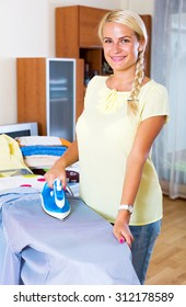 Portrait smiling housewife ironing clothing at home interior