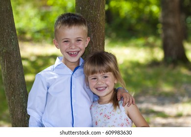 Portrait of a smiling hugging little girl and boy on a sunny day