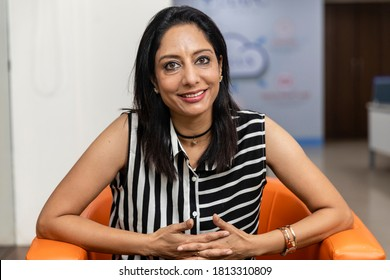 Portrait of smiling Indian business woman sitting on a couch and looking into camera, Corporate environment, smiling face.