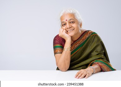 Portrait of smiling Indian woman in sari sitting at table
