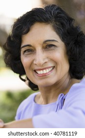 Portrait of a Smiling Indian Woman Sitting on a Bench in Park