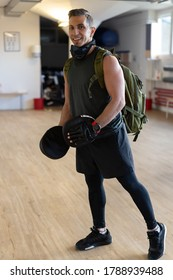 Portrait of smiling instructor with punching mitts in gym hall. Attractive sportsman looking to camera, for gym concept.