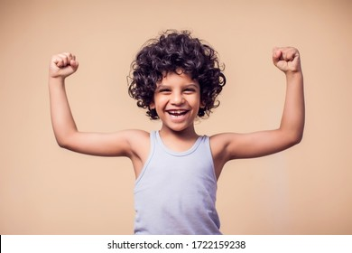A portrait of smiling kid boy with curly hair showing strong of hands. Children and health concept