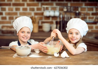 portrait of smiling kids in chef hats making dough for cookies